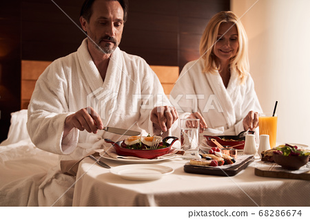 Calm couple enjoying meal in bed in the hotel room 68286674