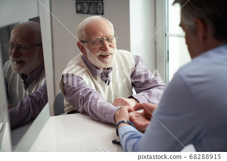 Senior citizen having his wrist checked by a healthcare worker 68288915