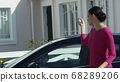 Trendy business woman locking her car. Video. Sexy elegant stylish lady wearing pink fashionable dress parking leaving her expensive car and getting inside beautiful cottage. 68289206