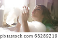 Young attractive woman blowing foam and playing with it. Video. Sun shining through the window in the bathroom where brunette taking bubble bath and relaxing. 68289219