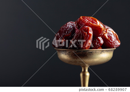 Closeup sweet dried dates in brass dish. 68289907