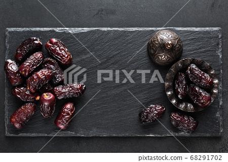 Dried dates on black slate background 68291702