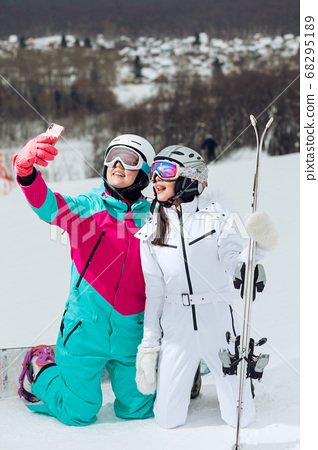 best female friends taking a selfie, happy tourists having fun while skiing 68295189