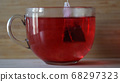 Dipping red tea bag in a transparent mug with hot water on wooden wall background. Concept. Close up of brewing of red karkade tea in a big cup with water. 68297323
