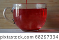 Dipping red tea bag in a transparent mug with hot water on wooden wall background. Concept. Close up of brewing of red karkade tea in a big cup with water. 68297334