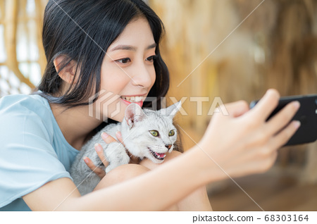 woman is playing with cat 68303164