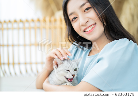 woman is playing with cat 68303179