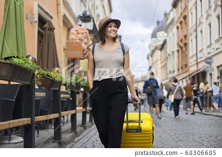Traveling smiling mature woman tourist in hat with backpack and suitcase walking 68306685