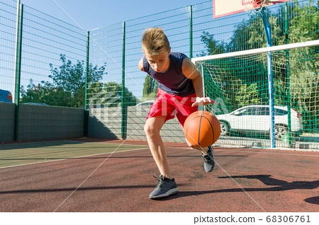Boy teenager playing basketball in city basketball court 68306761