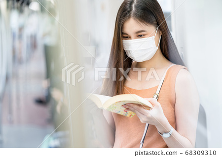 Young Asian woman passenger wearing surgical mask and reading the book in subway train when traveling in big city at Covid19 outbreak, Infection and Pandemic concept. 68309310
