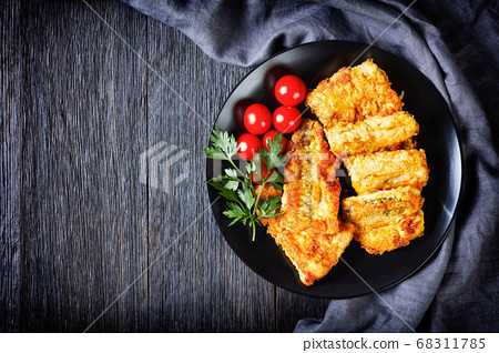 Cod fillet on black plate with cherry tomatoes 68311785