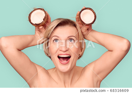 Mature Beauty. Woman standing isolated on blue playing with coconut laughing cheerful 68316609