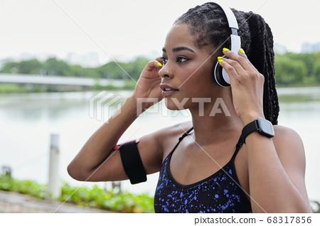 Sportswoman putting on headphnes 68317856