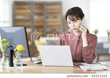 스마트 폰으로 통화하면서 PC 화면을 보는 젊은 여성 68321828