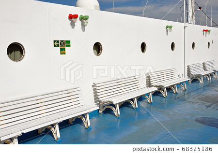 benches and portholes on ship deck 68325186