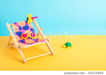 Beach chair wirh lovely sunglasses on the yellow ground with blue background. 68328809