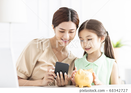 Mother with daughter watching the mobile phone and 68342727