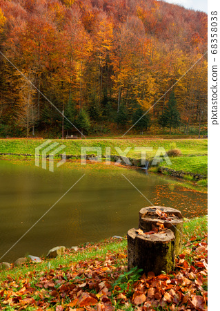small lake in autumn park. forest on the hills in 68358038