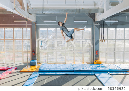 funny man trying to touch ceiling during the jumping 68366922
