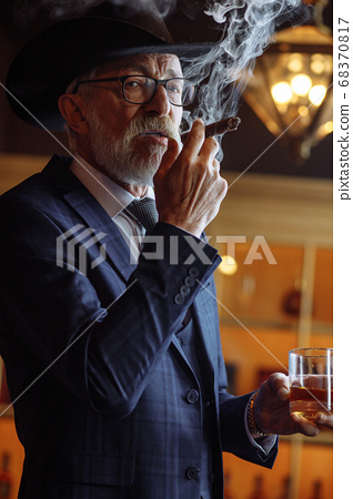 Portrait of old-aged male dandy in big hat smokes cigar and drin 68370817