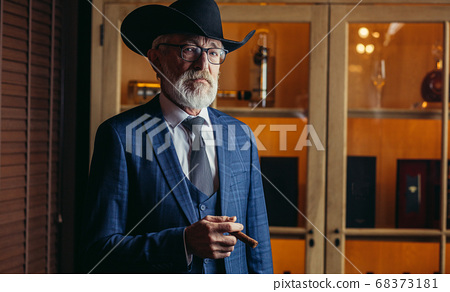 Stylish old man in wide brimmed hat and rich blue mens suit smok 68373181