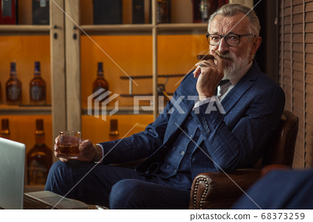 Elderly businessman with glass of whiskey and cigar on dark background 68373259