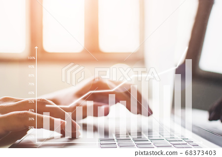 Hand using computer laptop analyzing sales data and economic growth graph chart 68373403
