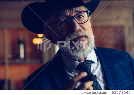 Stylish old man in wide brimmed hat and rich blue mens suit smok 68373646