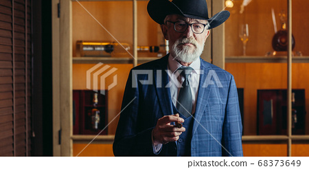 Stylish old man in wide brimmed hat and rich blue mens suit smok 68373649