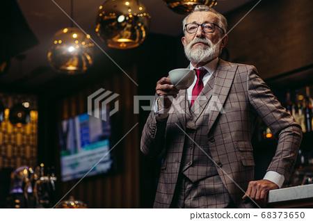 Senior businessman drinking coffee near bar counter at dark rest 68373650