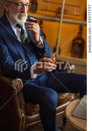 Elderly businessman with glass of whiskey and cigar on dark background 68373747