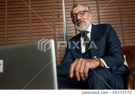 Senior dramatist looking at laptop, creating novel while sitting in pub. 68373770