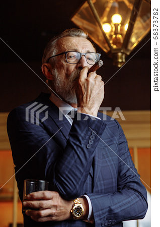 Elderly businessman in formal suit with whiskey and cigar at lux 68373782
