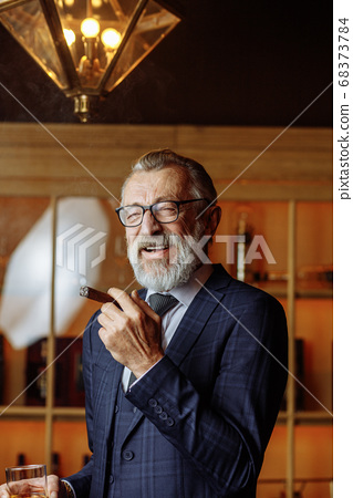 Elderly businessman in formal suit with whiskey and cigar at lux 68373784