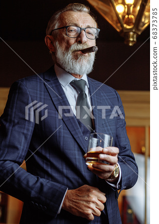 Elderly businessman in formal suit with whiskey and cigar at lux 68373785