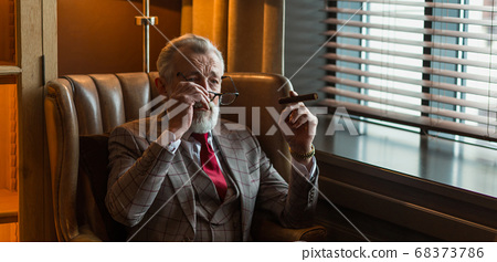 Serene concentrated mature male architector with grey-haired beard smoking cigar 68373786