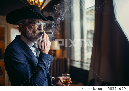 Stylish old man in wide brimmed hat and rich blue mens suit smoking cigar indoor 68374090