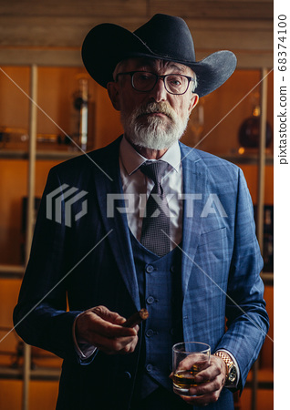 Stylish old man in wide brimmed hat and rich blue mens suit smok 68374100