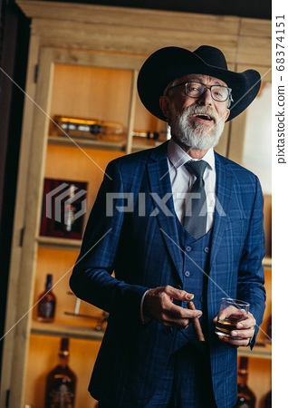 Portrait of old-aged male dandy in big hat smokes cigar and drin 68374151