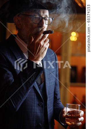 Portrait of old-aged male dandy in big hat smokes cigar and drin 68374153