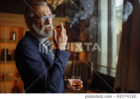 Elderly businessman in formal suit with whiskey and cigar at luxury interior 68374180