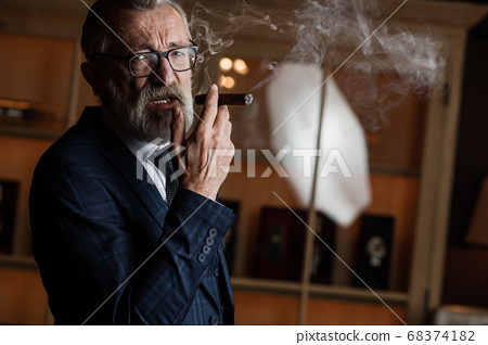 Elderly businessman in formal suit with whiskey and cigar at lux 68374182