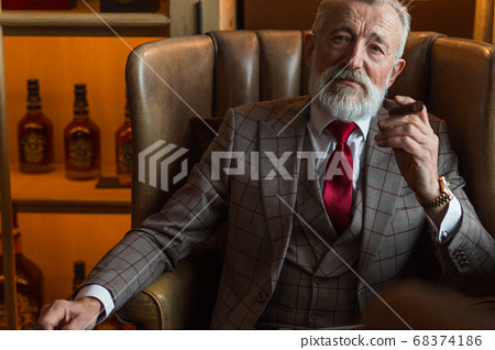 Serene concentrated mature male architector with grey-haired beard smoking cigar 68374186