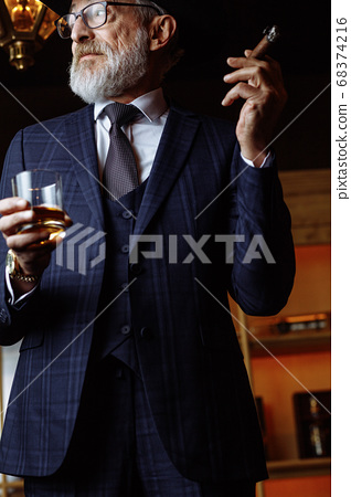 Stylish old man in wide brimmed hat and rich blue mens suit smok 68374216