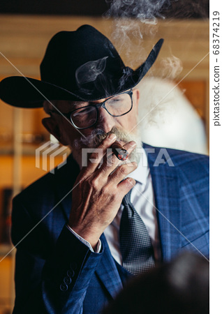 Stylish old man in wide brimmed hat and rich blue mens suit smok 68374219