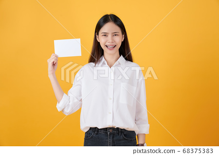 Young Asian woman holding blank paper with smiling face and looking on the yellow background. 68375383