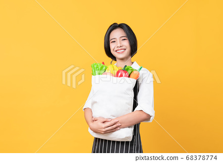 Woman in apron and standing holding white canvas bag with Vegetables and fruits on orange background 68378774