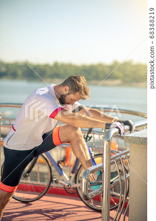 Attentive athletic man doing leg exercise near handrail 68388219