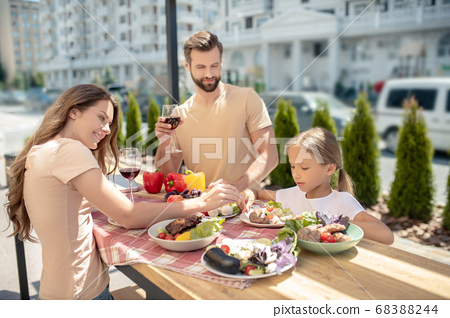 Young family having dinner outside and looking happy 68388244