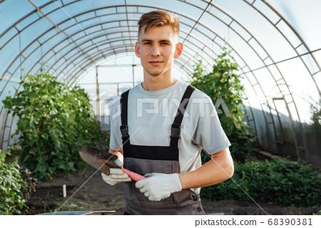 Man with garden tools.Young happy farmer posing 68390381